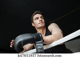 Thoughtful sportsman standing on ring