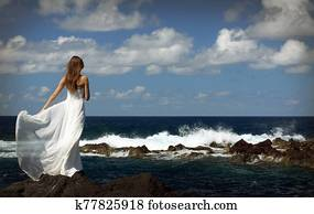 Young bride in light white wedding dress standing on sea rock shore and looking at ocean. Back view