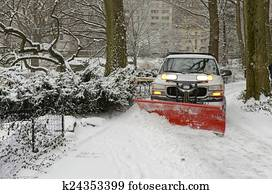 Truck with snowplow on road in snow