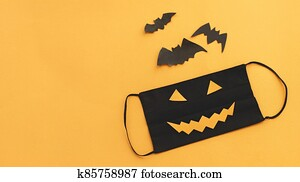 Evil face mask, bat and spider decorations on orange background with copy space. Stay safe