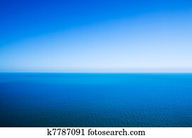 Idyllic abstract background - horizon line between calm sea and clear blue sky