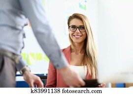 The woman with glasses sits in the office and smiles