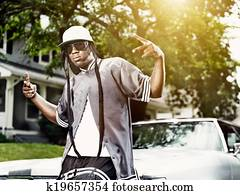 young black man making hand signs in front of car