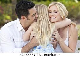 Girl Child Hugging Happy Parents In Park or Garden