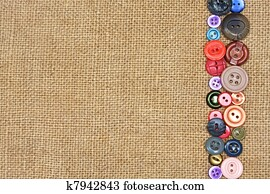 old colorful buttons on the background burlap
