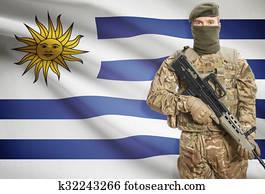 https://cdn-grid.fotosearch.com/CSP/CSP794/soldier-holding-machine-gun-with-flag-stock-photograph__k32243266.jpg