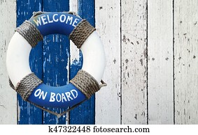 Welcome on board, lifebuoy on wooden background