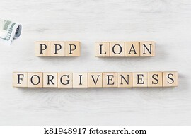 PPP LOAN Forgiveness text on wooden background with dollars roll
