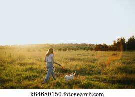 Stylish hipster girl walking with cute white puppy in summer meadow. Young woman on a walk with her doggy in warm sunshine light. Adoption concept, loyal friend