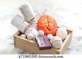 Beauty care products in wooden box. soap, towel with orange bath bomb. Spa or personal hygiene concept