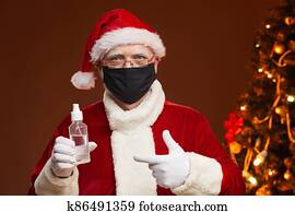 Santa Claus in mask and with antiseptic