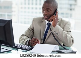 Smiling entrepreneur making a phone call while looking at his computer in his office