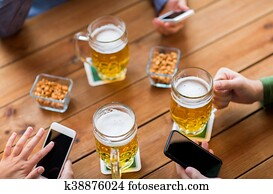 close up of hands with smartphones and beer at bar