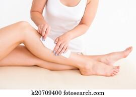 Female Therapist Waxing Customer's Leg