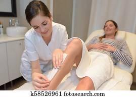 spa woman waxing her leg