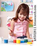 Child preschooler painting in classroom.