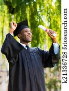 Finally graduated! Happy young African man in graduation gowns holding diploma and rising arms up