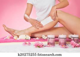 Therapist Waxing Customer's Leg At Spa