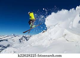 Alpine skier on piste, skiing downhill