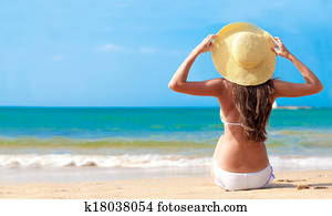 closeup back view young woman in bikini and hat with flower sitting on beach