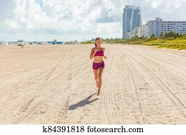 Fit woman training outdoors running barefoot on Miami south beach run jogging workout female Asian athlete. Happy healthy fitness person cardio jog in sun summer lifestyle