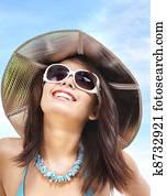 Girl in bikini and sunglasses on beach.