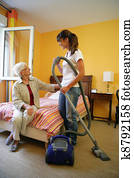 Cleaner vacuuming bedroom