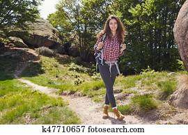 Woman hiking in summer forest in mountains