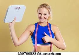 femme sportive heureuse avec échelle de perte de poids