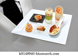 Catering waiter with canapes on pla