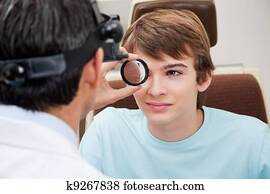 Optometrist performing Dilated Retinal Exam