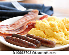 breakfast meal with sausage and scrambled eggs with bacon.