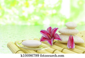 Flowers stones and soap near water in spa salon