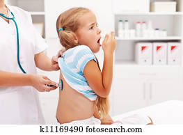 Little girl coughing at the doctor