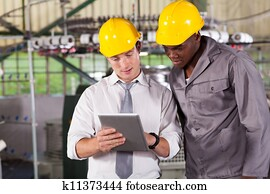 manager and worker looking at tablet computer