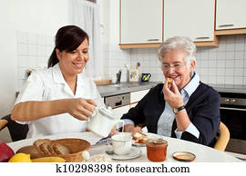 nurse helps elderly woman at breakfast