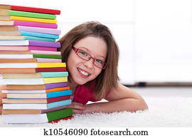 Young student with lots of books smiling