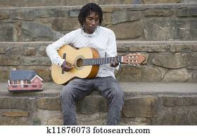 African busker playing guitar