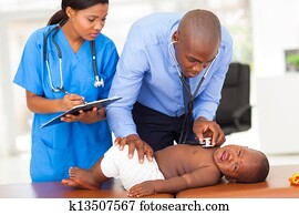 african pediatrician with nurse assistant examining a child