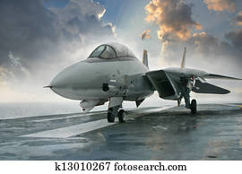 An F-14 Tomcat jet fighter sits on the deck of an aircraft carrier deck beneath dramatic clouds