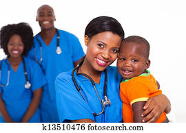 black pediatrician and baby boy with co-workers on background