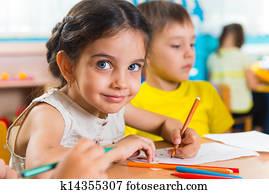 Group of cute little preschool kids drawing