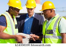 manager and construction workers examining a brick