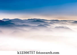 Misty mountains landscape view with blue sky