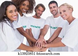 Smiling volunteer group putting hands together