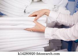 White Bedsheets Stacked In Stock Room