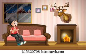 A boy sitting at the sofa near the fireplace