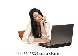 stock photo of bored business woman working on laptop looking very