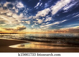 Calm ocean under dramatic sunset sky