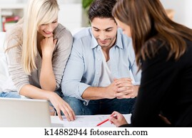 Financial Advisor Explaining Document To Couple At Table